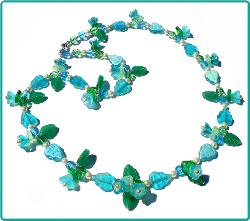 A custom floral necklace of aqua and green flower and leaf beads.